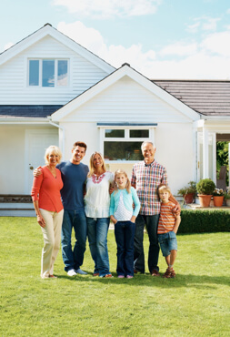 Multigeneration family stands on the front law of their home