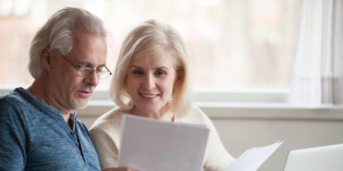 older couple smiling reviewing documents