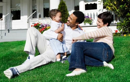 Mother and father play with toddler on their front lawn